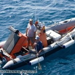 Willi Schlechter and John Schaefers repair the engine on the Squall RHIB