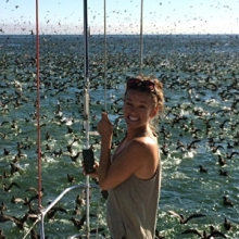 Erin Pickett at front of boat with birds feeding in the ocean in the background
